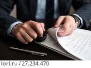 Купить «Мужчина ставит печать на документах», эксклюзивное фото № 27234470, снято 6 ноября 2017 г. (c) Игорь Низов / Фотобанк Лори