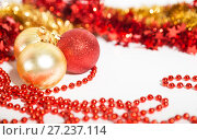 Купить «Christmas decorations of red and golden color on a white background - balls, beads and tinsel», фото № 27237114, снято 24 ноября 2017 г. (c) Юлия Бабкина / Фотобанк Лори
