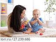 Купить «mom and baby playing musical toys at home», фото № 27239686, снято 24 ноября 2017 г. (c) Оксана Кузьмина / Фотобанк Лори