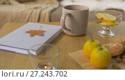 Купить «book, lemon, tea and cookies on table at home», видеоролик № 27243702, снято 23 ноября 2017 г. (c) Syda Productions / Фотобанк Лори