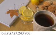 Купить «book, lemon, cup of tea, nuts and cookies on table», видеоролик № 27243706, снято 23 ноября 2017 г. (c) Syda Productions / Фотобанк Лори