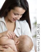 Купить «Young mother feeding breast her baby at home in white room», фото № 27245302, снято 24 ноября 2017 г. (c) Оксана Кузьмина / Фотобанк Лори