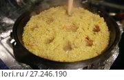Купить «Cooking pilaf, shef makes holes for the boiling of the pilaf in cast-iron kettle», видеоролик № 27246190, снято 2 октября 2017 г. (c) Ирина Мойсеева / Фотобанк Лори