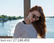Red-haired girl in sunglasses on background of the river. Стоковое фото, фотограф Вячеслав / Фотобанк Лори