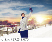 Купить «man taking selfie with smartphone in winter», фото № 27249670, снято 10 ноября 2016 г. (c) Syda Productions / Фотобанк Лори