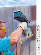 Купить «Man in overalls and protective glasses with spray gun in hand. Painting of metal fence», фото № 27250970, снято 17 августа 2014 г. (c) Евгений Ткачёв / Фотобанк Лори