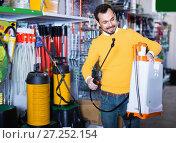 Купить «Young man choosing garden sprayer in garden equipment shop», фото № 27252154, снято 2 марта 2017 г. (c) Яков Филимонов / Фотобанк Лори