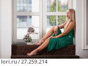 Купить «Девушка в зелёном платье сидит на подоконнике», фото № 27259214, снято 28 октября 2017 г. (c) Литвяк Игорь / Фотобанк Лори