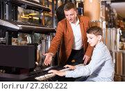 Купить «Seller recommends the buyer a keyboard», фото № 27260222, снято 29 марта 2017 г. (c) Яков Филимонов / Фотобанк Лори