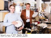 Купить «Boy and father choosing best drum», фото № 27260226, снято 29 марта 2017 г. (c) Яков Филимонов / Фотобанк Лори