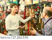 Купить «Ordinary customer and friendly seller choosing hammer», фото № 27262510, снято 19 ноября 2018 г. (c) Яков Филимонов / Фотобанк Лори