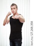 Купить «Handsome blond man with boxer pose with fist up stands on white background», фото № 27268358, снято 4 марта 2012 г. (c) Кекяляйнен Андрей / Фотобанк Лори
