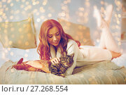 Купить «happy young woman with cat lying in bed at home», фото № 27268554, снято 15 октября 2016 г. (c) Syda Productions / Фотобанк Лори