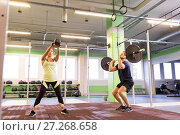 Купить «man and woman with weights exercising in gym», фото № 27268658, снято 19 февраля 2017 г. (c) Syda Productions / Фотобанк Лори