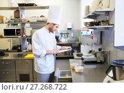 Купить «chef with clipboard doing inventory at kitchen», фото № 27268722, снято 2 апреля 2017 г. (c) Syda Productions / Фотобанк Лори