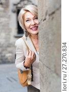 Купить «Elegant mature woman is posing near old wall», фото № 27270834, снято 3 сентября 2017 г. (c) Яков Филимонов / Фотобанк Лори