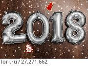 Купить «Bright metallic silver balloons figures 2018, Christmas, New Year Balloon with glitter stars on dark wood table background», фото № 27271662, снято 19 ноября 2017 г. (c) Сергей Тимофеев / Фотобанк Лори