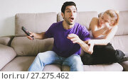Купить «Young upset woman trying to take away TV remote from her boyfriend», видеоролик № 27275462, снято 17 октября 2017 г. (c) Яков Филимонов / Фотобанк Лори