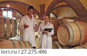 Купить «Winery workers in white robes controlling fermantation process of wine», видеоролик № 27275486, снято 3 октября 2016 г. (c) Яков Филимонов / Фотобанк Лори