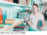 Купить «Charming female buying products in stationery shop», фото № 27277086, снято 9 мая 2017 г. (c) Яков Филимонов / Фотобанк Лори