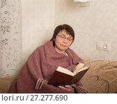 Купить «Женщина пенсионного возраста читает книгу, укутавшись пледом», фото № 27277690, снято 10 декабря 2017 г. (c) Юлия Бабкина / Фотобанк Лори