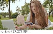 Купить «Pretty young student girl makes purchases online using a credit card and laptop computer», видеоролик № 27277994, снято 21 октября 2017 г. (c) Mikhail Davidovich / Фотобанк Лори
