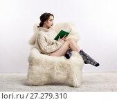 Купить «Brunette woman on furry arm-chair with book in hands», фото № 27279310, снято 8 октября 2017 г. (c) Serg Zastavkin / Фотобанк Лори