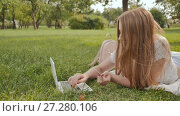 Купить «A young student girl makes payments with a credit card and laptop while lying on the grass in a city park», видеоролик № 27280106, снято 21 октября 2017 г. (c) Mikhail Davidovich / Фотобанк Лори