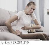 Купить «Young woman is sitting with spasm because she has a stomach ache», фото № 27281210, снято 4 октября 2017 г. (c) Яков Филимонов / Фотобанк Лори