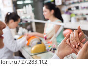 Купить «Manicurist inspecting female hands», фото № 27283102, снято 28 апреля 2017 г. (c) Яков Филимонов / Фотобанк Лори