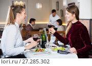 Купить «Two girls meeting in restaurant», фото № 27285302, снято 7 ноября 2017 г. (c) Яков Филимонов / Фотобанк Лори