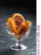 Купить «Caramelized oranges in a delicate glass crockery.», фото № 27286238, снято 20 ноября 2017 г. (c) Olesya Tseytlin / Фотобанк Лори