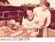 Купить «Glad couple deciding on fruits in shop», фото № 27288578, снято 23 ноября 2016 г. (c) Яков Филимонов / Фотобанк Лори