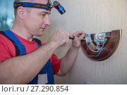 Купить «Male electrician connects the lamp on the wall», фото № 27290854, снято 21 мая 2017 г. (c) Наталья Давыдова / Фотобанк Лори