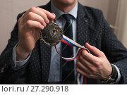 Купить «Мужчина держит в руках медаль за 2 место. Фокус на медали», эксклюзивное фото № 27290918, снято 6 ноября 2017 г. (c) Игорь Низов / Фотобанк Лори