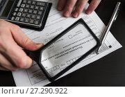 Купить «Бизнесмен рассматривает налоговую декларацию на вменённый доход через лупу», эксклюзивное фото № 27290922, снято 6 ноября 2017 г. (c) Игорь Низов / Фотобанк Лори