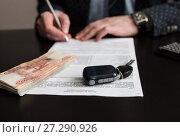 Купить «Покупка автомобиля. Российские деньги и автомобильный ключ от зажигания машины лежат на договоре купли продажи», эксклюзивное фото № 27290926, снято 6 ноября 2017 г. (c) Игорь Низов / Фотобанк Лори
