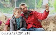 Купить «Happy father and daughter sitting on sofa making funny faces while taking selfie 4K 4k», видеоролик № 27291218, снято 10 декабря 2018 г. (c) Wavebreak Media / Фотобанк Лори