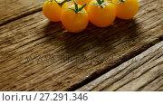 Купить «Yellow cherry tomatoes with stem on wooden floor 4K 4k», видеоролик № 27291346, снято 19 февраля 2018 г. (c) Wavebreak Media / Фотобанк Лори