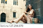 Купить «young happy female in rose dress sitting in city», видеоролик № 27294070, снято 8 сентября 2017 г. (c) Яков Филимонов / Фотобанк Лори
