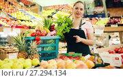 Young smiling saleswoman offering fresh fruits and vegetables in store. Стоковое видео, видеограф Яков Филимонов / Фотобанк Лори