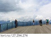 Купить «Туристы, стоящие на обзорной площадке Роза Пик горнолыжного курорта Роза Хутор в горах Кавказа. Пасмурный летний день», фото № 27294274, снято 10 июня 2017 г. (c) Наталья Гармашева / Фотобанк Лори