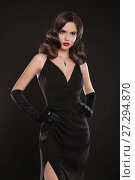 Купить «Fashionable model. Elegant lady in long sexy dress with retro wavy hairstyle posing isolated on studio black background. Beautiful brunette woman in glamour gloves. Fashion style photo.», фото № 27294870, снято 1 декабря 2017 г. (c) Photobeauty / Фотобанк Лори