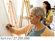 senior woman drawing on easel at art school studio. Стоковое фото, фотограф Syda Productions / Фотобанк Лори