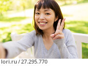 Купить «happy asian woman taking selfie and showing peace», фото № 27295770, снято 24 августа 2017 г. (c) Syda Productions / Фотобанк Лори