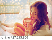 happy woman with cup of cocoa in bed at home. Стоковое фото, фотограф Syda Productions / Фотобанк Лори