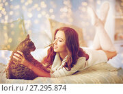 Купить «happy young woman with cat lying in bed at home», фото № 27295874, снято 15 октября 2016 г. (c) Syda Productions / Фотобанк Лори