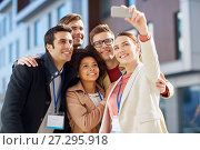 Купить «business team with conference badges taking selfie», фото № 27295918, снято 13 мая 2017 г. (c) Syda Productions / Фотобанк Лори