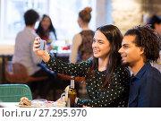 Купить «happy couple taking selfie at restaurant or bar», фото № 27295970, снято 19 ноября 2016 г. (c) Syda Productions / Фотобанк Лори