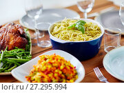 Купить «pasta with basil in bowl and other food on table», фото № 27295994, снято 5 октября 2017 г. (c) Syda Productions / Фотобанк Лори